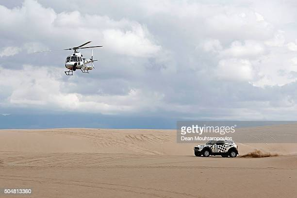 Mikko Hirvonen of Finland and Michel Perin of France in the MINI ALL4 RACING for AXION XRAID TEAM are followed by the TV helicopter as they compete...