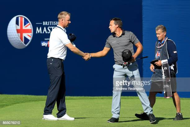 Mikko Ilonen of Finland and Chris Hanson of England shake hands on the 18th green after finishing their rounds during day one of the British Masters...