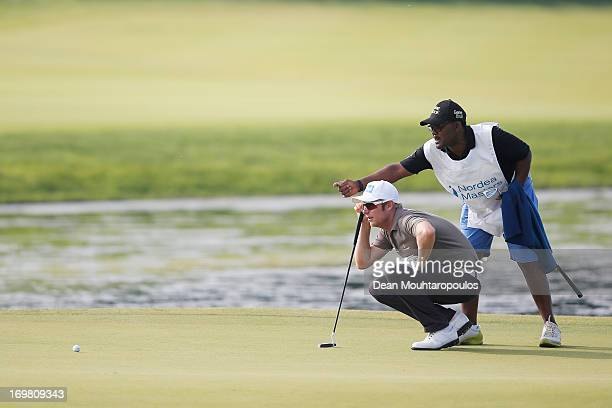 Mikko Ilonen of Finland and his caddie Reginald Mokhosi line up a putt on the 17th green during the Nordea Scandinavian Masters at Bro Hof Slott Golf...