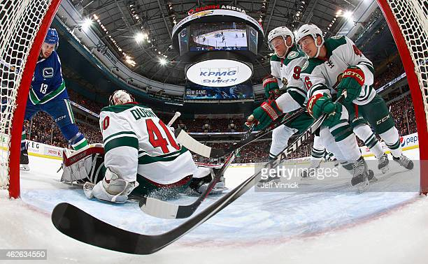 Mikko Koivu and Jared Spurgeon of the Minnesota Wild ensure a shot by Nick Bonino of the Vancouver Canucks doesn't slide behind Devan Dubnyk of the...