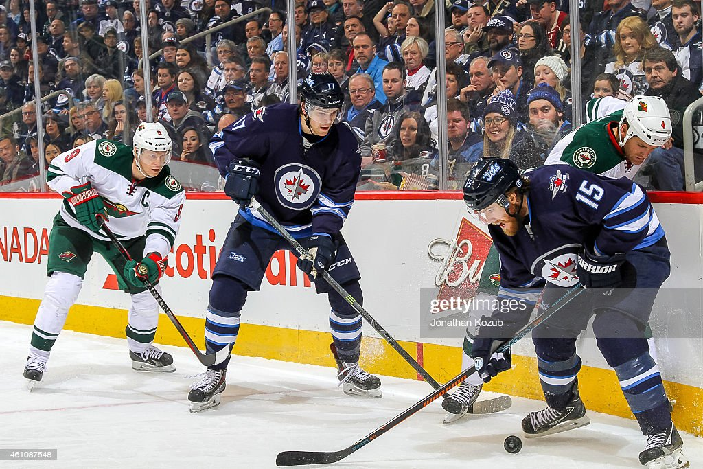<a gi-track='captionPersonalityLinkClicked' href=/galleries/search?phrase=Mikko+Koivu&family=editorial&specificpeople=584987 ng-click='$event.stopPropagation()'>Mikko Koivu</a> #9 of the Minnesota Wild and Adam Lowry #17 of the Winnipeg Jets look on as teammates <a gi-track='captionPersonalityLinkClicked' href=/galleries/search?phrase=Stu+Bickel&family=editorial&specificpeople=4862669 ng-click='$event.stopPropagation()'>Stu Bickel</a> #4 and <a gi-track='captionPersonalityLinkClicked' href=/galleries/search?phrase=Matt+Halischuk&family=editorial&specificpeople=714406 ng-click='$event.stopPropagation()'>Matt Halischuk</a> #15 battle for the puck along the boards during third period action on December 29, 2014 at the MTS Centre in Winnipeg, Manitoba, Canada. The Wild defeated the Jets 3-2.