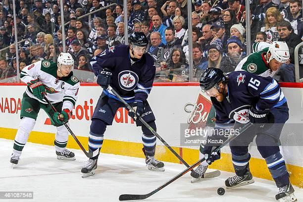 Mikko Koivu of the Minnesota Wild and Adam Lowry of the Winnipeg Jets look on as teammates Stu Bickel and Matt Halischuk battle for the puck along...