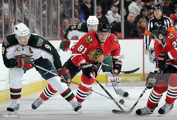 Mikko Koivu of the Minnesota Wild and Marian Hossa of the Chicago Blackhawks reach for the puck as Dave Bolland of the Blackhawks turns to watch on...