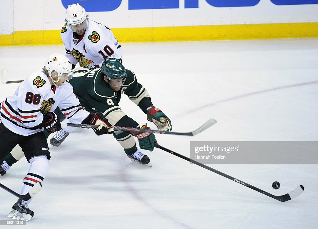 Mikko Koivu #9 of the Minnesota Wild controls the puck against Patrick Kane #88 and Patrick Sharp #10 of the Chicago Blackhawks during the third period in Game Three of the Second Round of the 2014 NHL Stanley Cup Playoffs on May 6, 2014 at Xcel Energy Center in St Paul, Minnesota. The Wild defeated the Blackhawks 4-0.