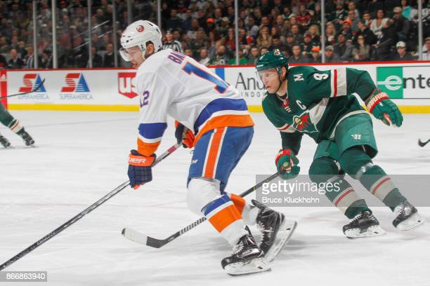 Mikko Koivu of the Minnesota Wild defends Josh Bailey of the New York Islanders during the game at the Xcel Energy Center on October 26 2017 in St...