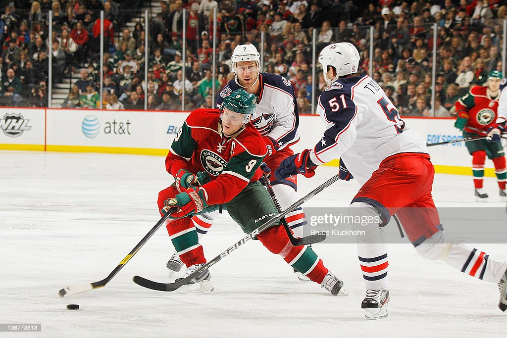 <a gi-track='captionPersonalityLinkClicked' href=/galleries/search?phrase=Mikko+Koivu&family=editorial&specificpeople=584987 ng-click='$event.stopPropagation()'>Mikko Koivu</a> #9 of the Minnesota Wild handles the puck with (L-R) <a gi-track='captionPersonalityLinkClicked' href=/galleries/search?phrase=Jeff+Carter&family=editorial&specificpeople=227320 ng-click='$event.stopPropagation()'>Jeff Carter</a> #7 and <a gi-track='captionPersonalityLinkClicked' href=/galleries/search?phrase=Fedor+Tyutin&family=editorial&specificpeople=215245 ng-click='$event.stopPropagation()'>Fedor Tyutin</a> #51 of the Columbus Blue Jackets defending during the game at the Xcel Energy Center on February 11, 2012 in St. Paul, Minnesota.