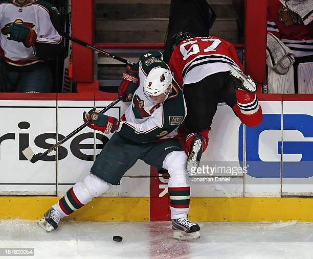 Mikko Koivu of the Minnesota Wild knocks Michael Frolik of the Chicago Blackhawks over the boards while trying to control the puck in Game One of the...