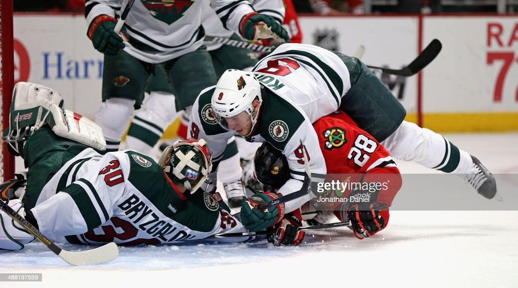 Mikko Koivu #9 of the Minnesota Wild lands on top of Ben Smith #28 of the Chicago Blackhawks as Smith tries to dislodge the puck from under Iiya Bryzgalov #30 in Game Two of the Second Round of the 2014 NHL Stanley Cup Playoffs at the United Center on May 4, 2014 in Chicago, Illinois. The Blackhawks defeated the Wild 4-1.