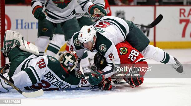 Mikko Koivu of the Minnesota Wild lands on top of Ben Smith of the Chicago Blackhawks as Smith tries to dislodge the puck from under Iiya Bryzgalov...