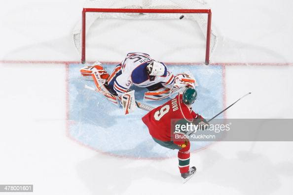 Mikko Koivu of the Minnesota Wild scores a shootout goal against Viktor Fasth of the Edmonton Oilers on March 11 2014 at the Xcel Energy Center in St...