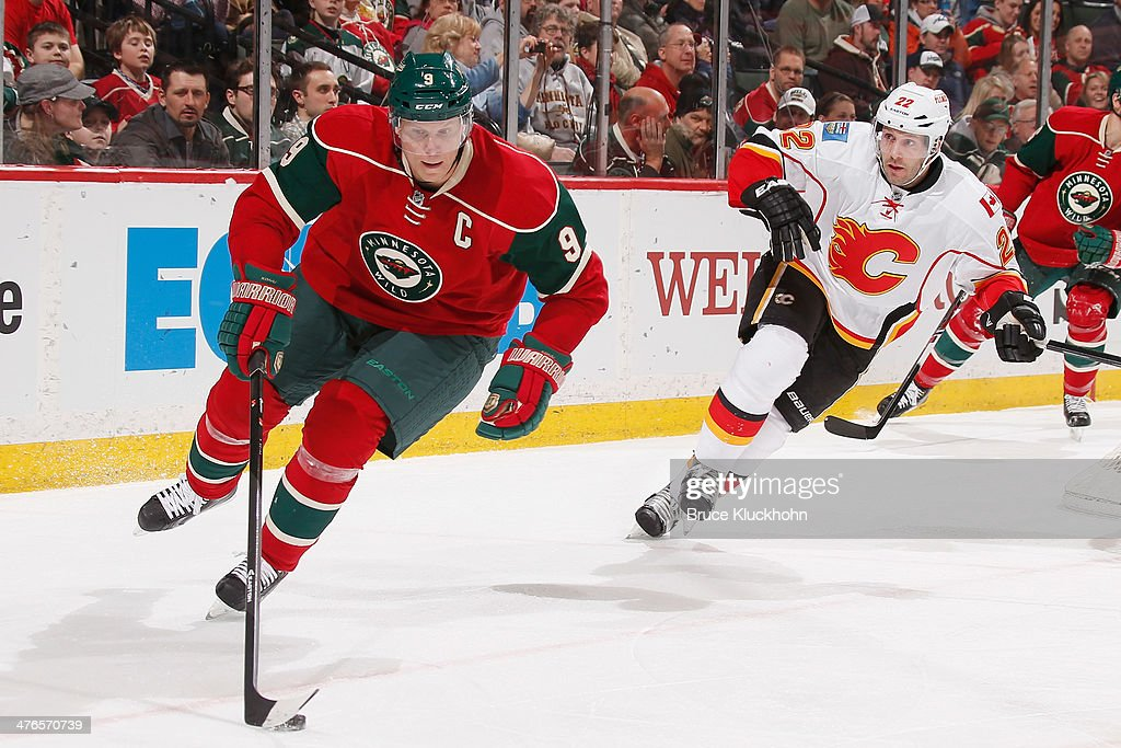 <a gi-track='captionPersonalityLinkClicked' href=/galleries/search?phrase=Mikko+Koivu&family=editorial&specificpeople=584987 ng-click='$event.stopPropagation()'>Mikko Koivu</a> #9 of the Minnesota Wild skates with the puck while <a gi-track='captionPersonalityLinkClicked' href=/galleries/search?phrase=Lee+Stempniak&family=editorial&specificpeople=575240 ng-click='$event.stopPropagation()'>Lee Stempniak</a> #22 of the Calgary Flames defends during the game on March 3, 2014 at the Xcel Energy Center in St. Paul, Minnesota.