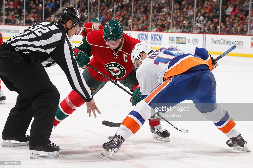 Mikko Koivu #9 of the Minnesota Wild takes a face-off against Peter Regin #16 of the New York Islanders during the game on December 29, 2013 at the Xcel Energy Center in St. Paul, Minnesota.