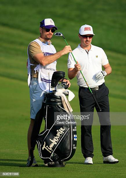 Mikko Korhonen of Finland chooses his club for his second shot on the par 5 10th hole during the first round of the 2016 Omega Dubai Desert Classic...
