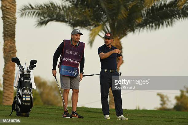 Mikko Korhonen of Finland consults with his caddie on the second hole during the second round of the Commercial Bank Qatar Masters at the Doha Golf...