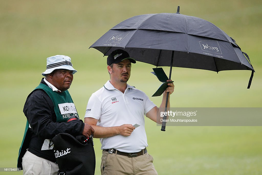 Mikko Korhonen of Finland holds his umbrella on before he hits his second shot on the 7th hole during Day Two of the Africa Open at East London Golf Club on February 15, 2013 in East London, South Africa.