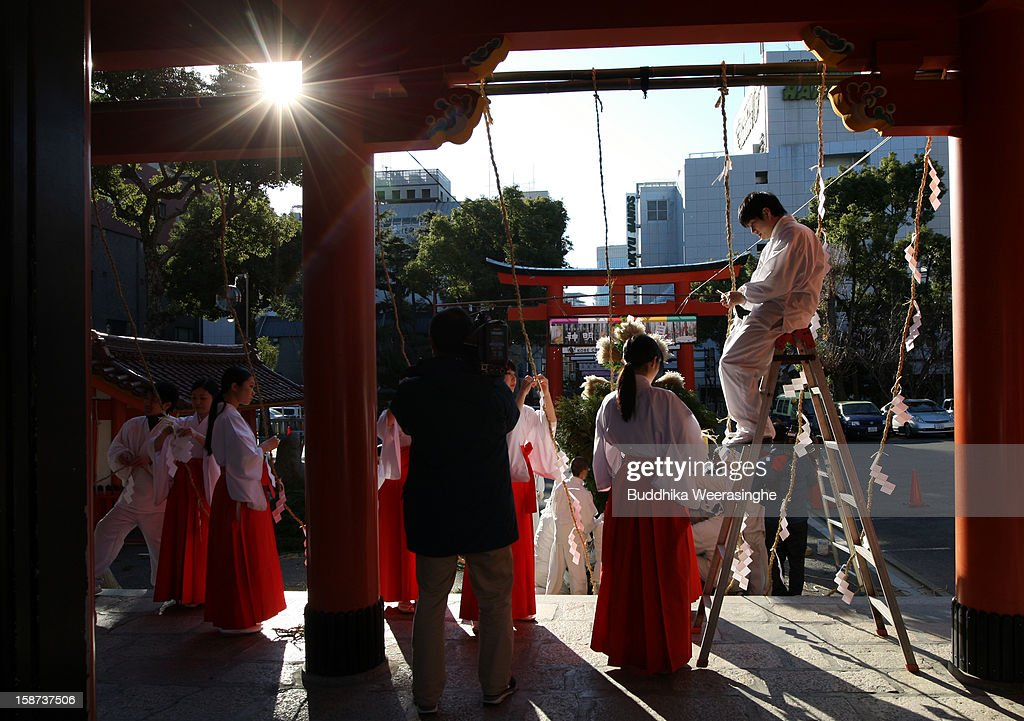 Miko (shrine maidens) and shrine priests decorate shrine entrance for celebration of the forthcoming 'Year of the Snake' at Ikuta Shrine on December 27, 2012 in Kobe, Japan. Japanese years are commonly associated with the twelve animals Mouse, Cow, Tiger, Rabbit, Dragon, Snake, Horse, Sheep, Monkey, Rooster, Dog and Pig.