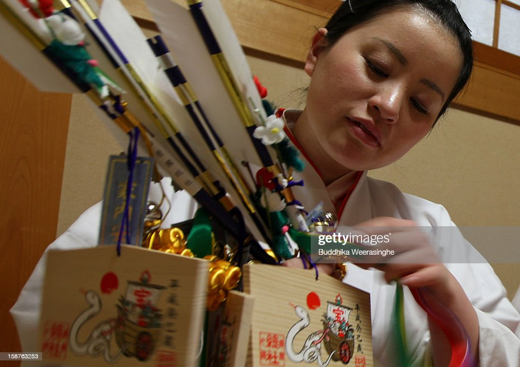 A Miko (shrine maidens) arranges 'Hamaya' (arrows intended to destroy evil spirits) to which 'Emas' (wooden plaques) are attached featuring a picture of a dragon in celebration of the forthcoming 'Year of the Snake' at Sosha Shrine on December 28, 2012 in Himeji, Japan. Japanese years are commonly associated with the twelve animals Mouse, Cow, Tiger, Rabbit, Dragon, Snake, Horse, Sheep, Monkey, Rooster, Dog and Pig.