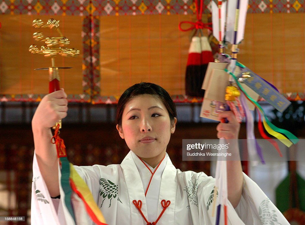 A Miko (Shrine maiden) blesses the 'Hamaya' (arrows intended to destroy evil spirits) to which 'Emas' (wooden plaques) are attached featuring a picture of a snake in celebration of the 'Year of the Snake' at Sosha Shrine on January 1, 2013 in Himeji, Japan. Japanese people visit the Buddhist temples and Shrine to pray for their health, happiness and prosperity during the New Year holidays.
