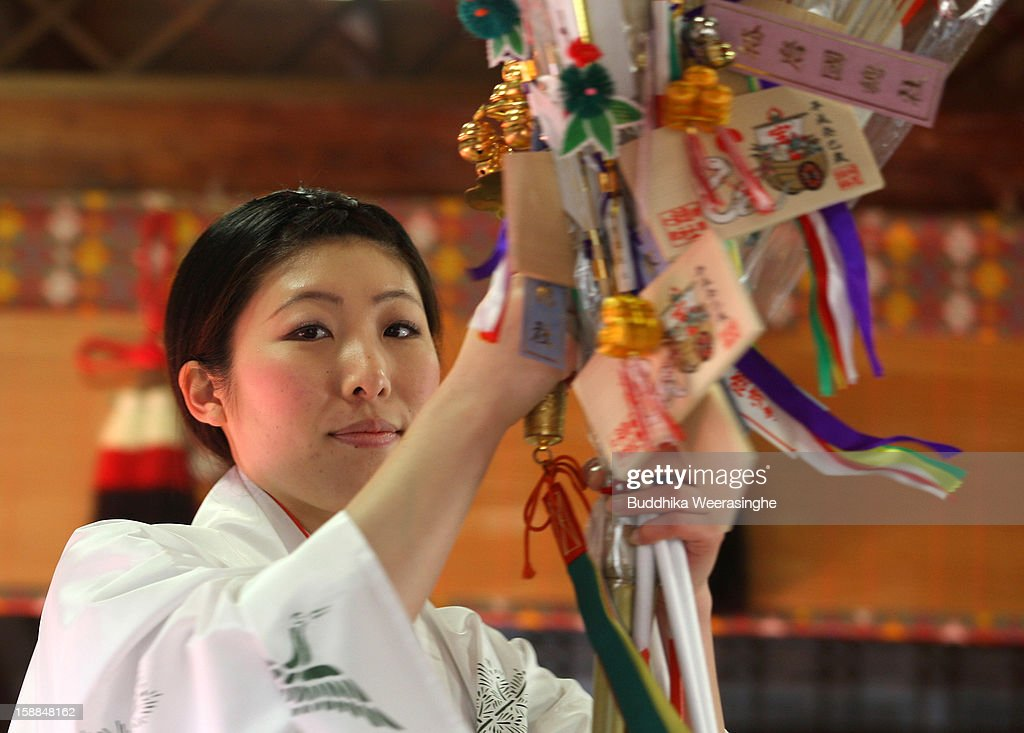 A Miko (Shrine maiden) blesses the 'Hamaya' (arrows intended to destroy evil spirits) to which 'Emas' (wooden plaques) are attached featuring a picture of a snake in celebration of the Year of the Snake at Sosha Shrine on January 1, 2013 in Himeji, Japan. Japanese people visit the Buddhist temples and shrine to pray for their health, happiness and prosperity during the New Year holidays.