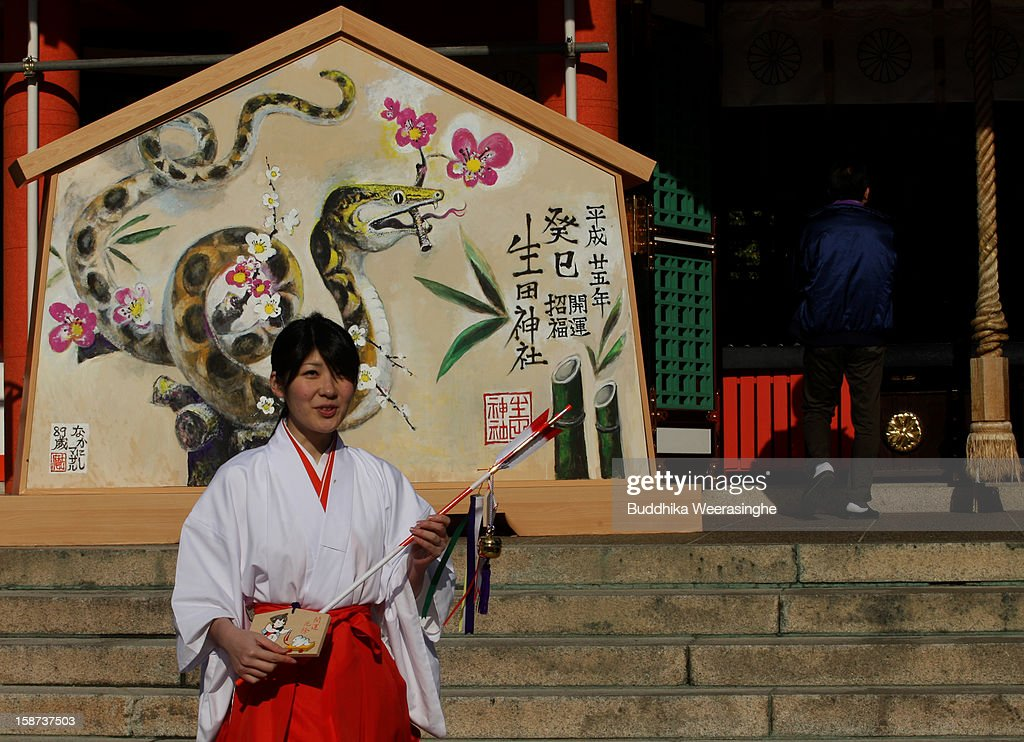 A Miko (shrine maidens) holds 'Hamaya' (arrows intended to destroy evil spirits) to which 'Emas' (wooden plaques) as she walks in front of a picture of snake in celebration of the forthcoming 'Year of the Snake' at Ikuta Shrine on December 27, 2012 in Kobe, Japan. Japanese years are commonly associated with the twelve animals Mouse, Cow, Tiger, Rabbit, Dragon, Snake, Horse, Sheep, Monkey, Rooster, Dog and Pig.