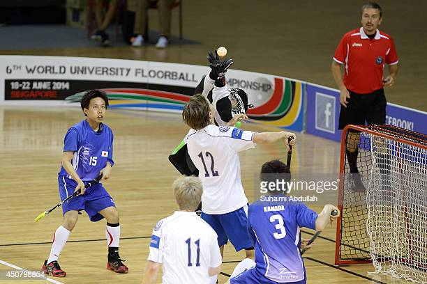 Miko Kailiala of Finland and Kenta Higuchi of Japan challenge for the ball during the World University Championship Floorball match between Japan and...