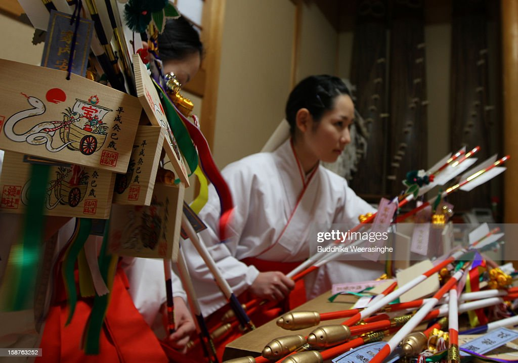 Mikos (shrine maidens) arrange 'Hamaya' (arrows intended to destroy evil spirits) to which 'Emas' (wooden plaques) are attached featuring a picture of a dragon in celebration of the forthcoming 'Year of the Snake' at Sosha Shrine on December 28, 2012 in Himeji, Japan. Japanese years are commonly associated with the twelve animals Mouse, Cow, Tiger, Rabbit, Dragon, Snake, Horse, Sheep, Monkey, Rooster, Dog and Pig.