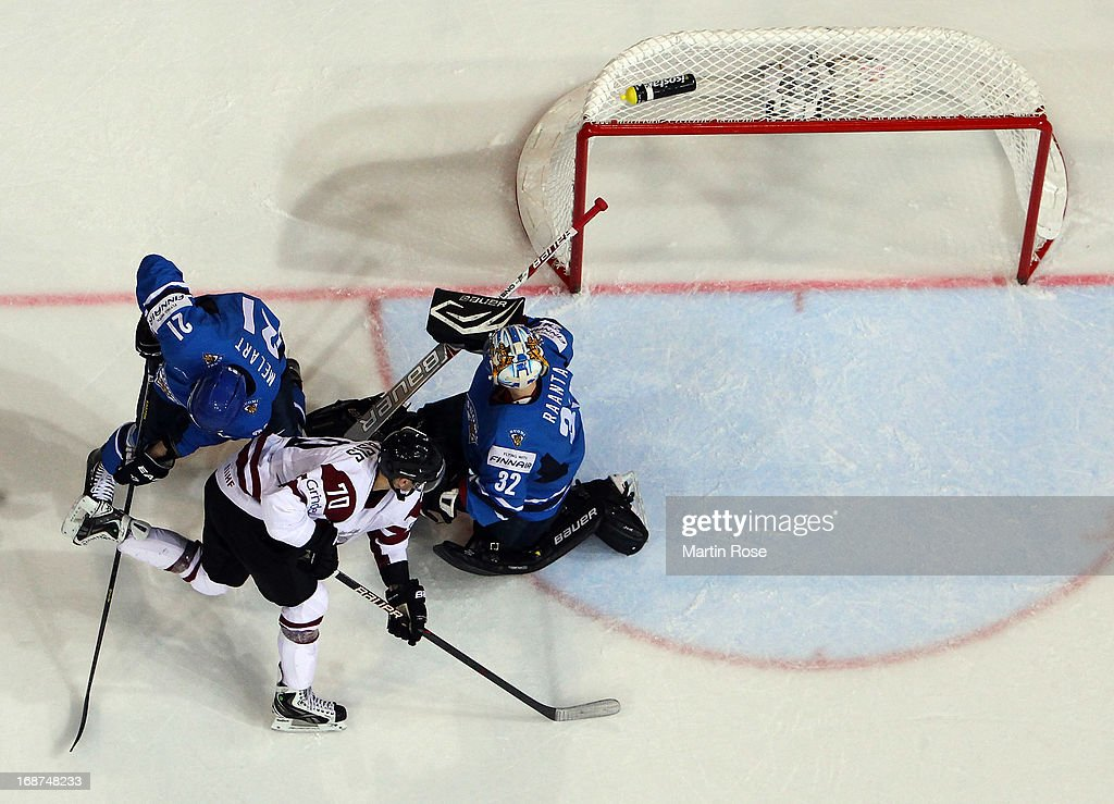 Miks Indrasis (#70) of Latvia and Ilari Melart (#21) of Finland battle for the puck during the IIHF World Championship group H match between Latvia and Finland at Hartwall Areena on May 14, 2013 in Helsinki, Finland.