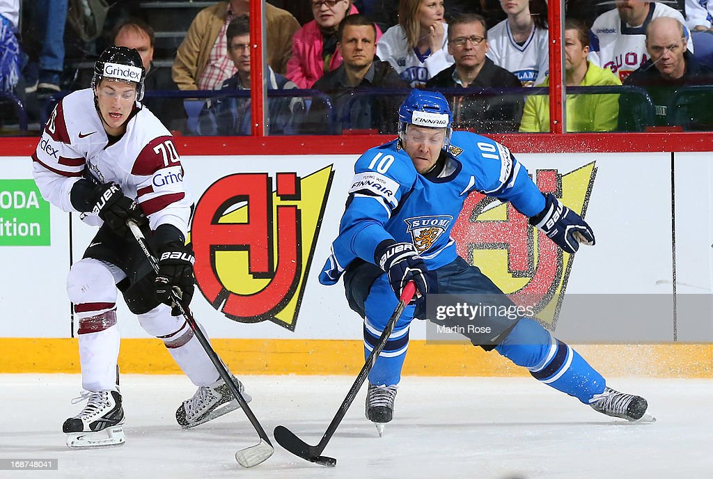Miks Indrasis (L) of Latvia and Niklas Hagman (R) of Finland battle for the puck during the IIHF World Championship group H match between Latvia and Finland at Hartwall Areena on May 14, 2013 in Helsinki, Finland.