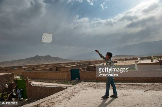 Milad flies a kite on top of his house in the mostly abandoned land allocation settlement of AliceGhan about 30 miles outside of Kabul Afghanistan...