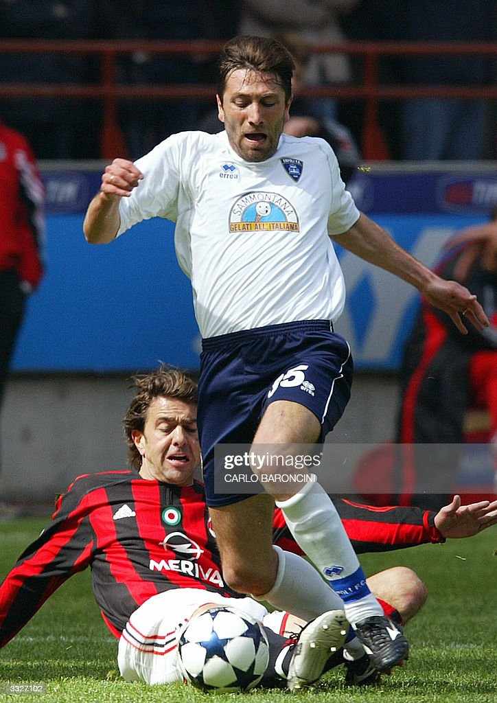 AC Milan Alessandro Costacurta (L) tackles Antonio Busce (R) of Empoli during their Italian Serie A football match at Empoli's stadium 10 April 2004. AFP PHOTO/Carlo BARONCINI