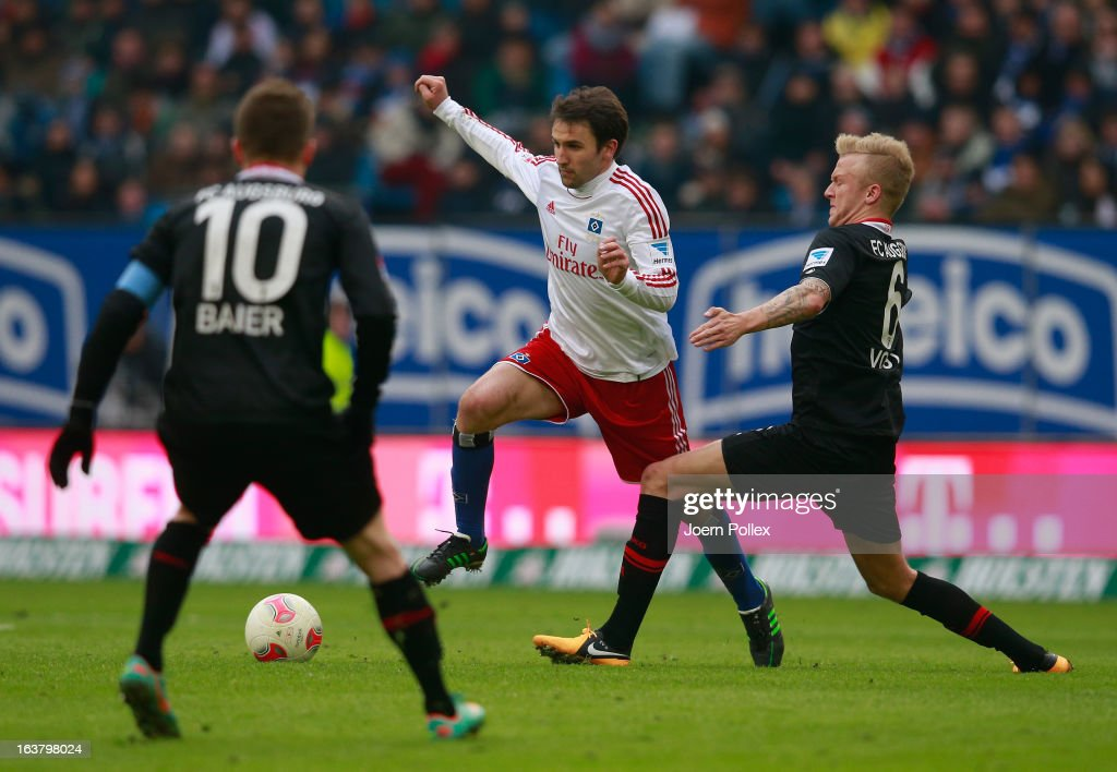 Milan Badelj (C) of Hamburg and Kevin Vogt of Augsburg compete for the ball during the Bundesliga match between Hamburger SV and FC Augsburg at Imtech Arena on March 16, 2013 in Hamburg, Germany.