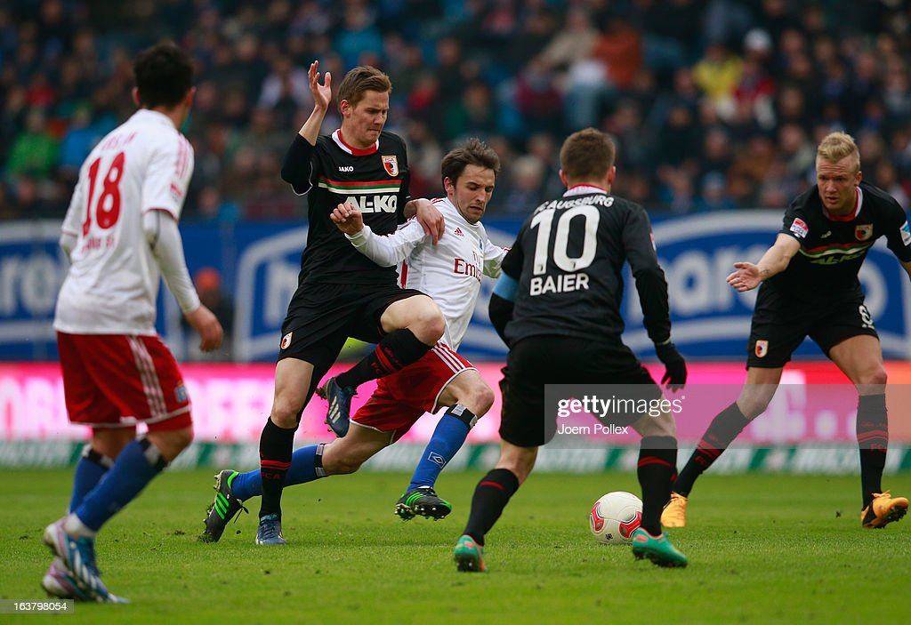 Milan Badelj (C) of Hamburg and Torsten Oehrl of Augsburg compete for the ball during the Bundesliga match between Hamburger SV and FC Augsburg at Imtech Arena on March 16, 2013 in Hamburg, Germany.