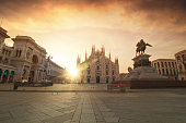 Street view of Piazza del Duomo in Milan, clouds are visible over the cathedral at dawn. The monument statue of Vittorio Emanuele II is visible on the right side of the frame.