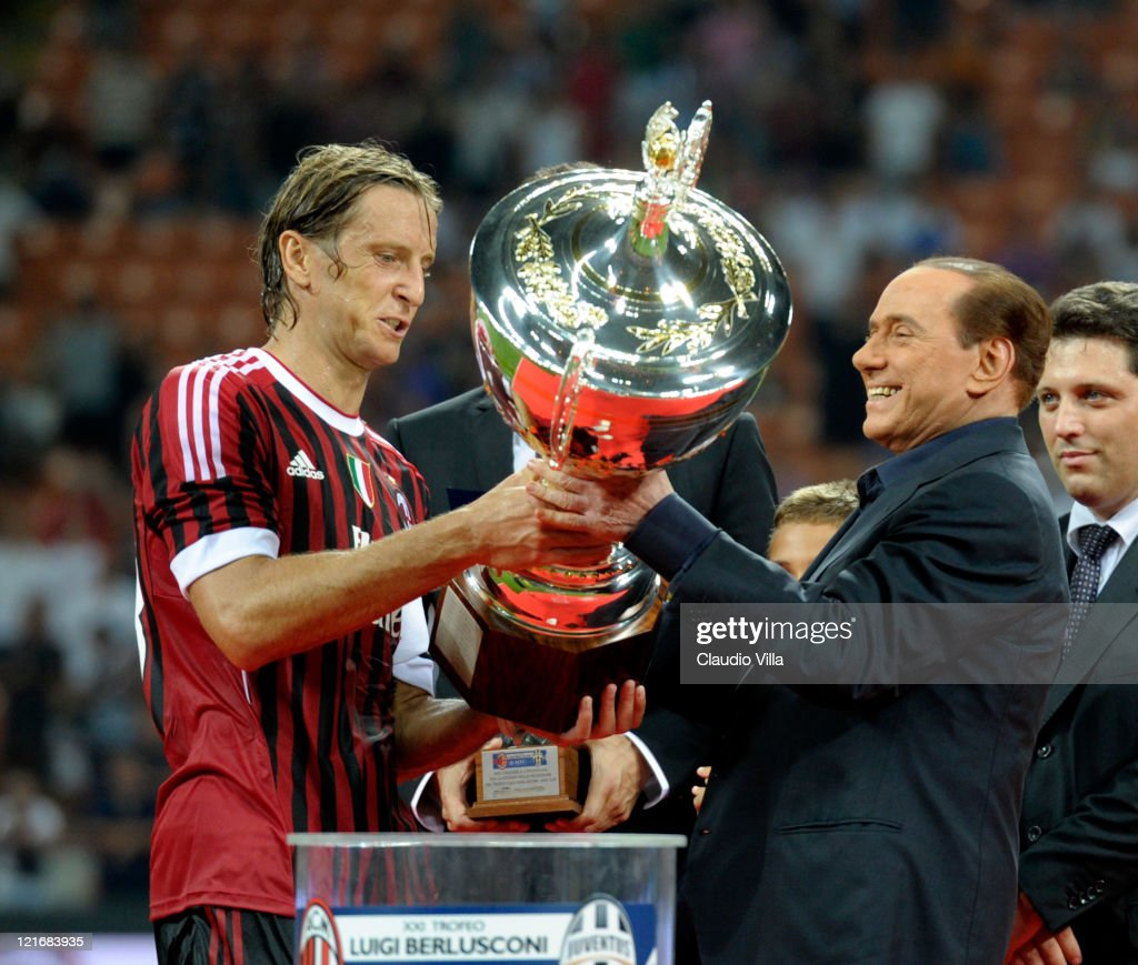 AC Milan chairman <a gi-track='captionPersonalityLinkClicked' href=/galleries/search?phrase=Silvio+Berlusconi&family=editorial&specificpeople=201842 ng-click='$event.stopPropagation()'>Silvio Berlusconi</a> and <a gi-track='captionPersonalityLinkClicked' href=/galleries/search?phrase=Massimo+Ambrosini&family=editorial&specificpeople=227979 ng-click='$event.stopPropagation()'>Massimo Ambrosini</a> celebrate after winning the Berlusconi Trophy during the Berlusconi Trophy match between AC Milan and Juventus FC at Giuseppe Meazza Stadium on August 21, 2011 in Milan, Italy.