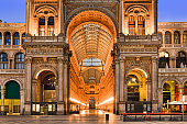 Entrance portico and facade of Vittorio Emmanuele gallery shopping district in Milan, Italy - the oldest shopping mall in the world on Cathedral square.