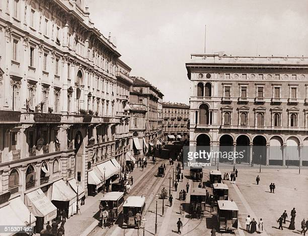An animated view of the corner pf the Plaza of the Duomo in Milan Trolley cars run on tracks next to the buildings Ca 1890