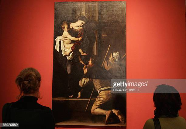 Women look at Italian painter Caravaggio's 'Madonna di Loreto' in Palazzo Reale during an exhibition called Caravaggio and Europe in Milan 14 October...