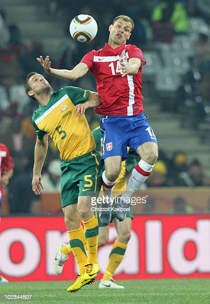 Milan Jovanovic of Serbia jumps for the ball as Jason Culina of Australia looks on during the 2010 FIFA World Cup South Africa Group D match between...