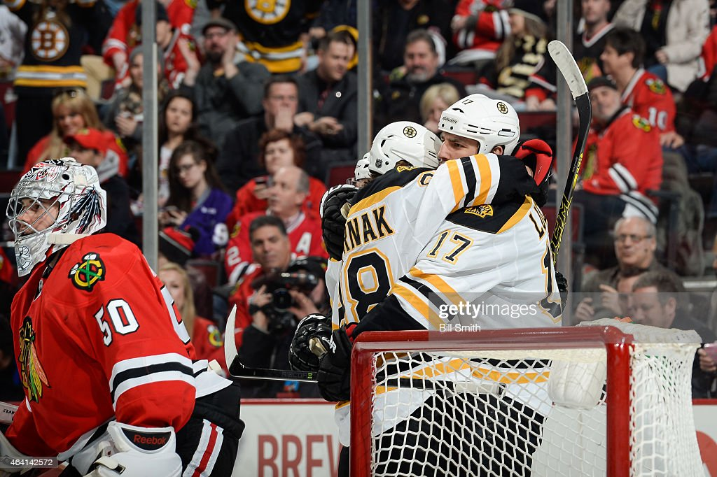 Milan Lucic and David Pastrnak of the Boston Bruins hug behind goalie Corey Crawford of the Chicago Blackhawks after Lucic scored against the...