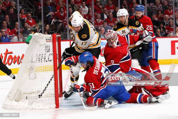 Milan Lucic and Jarome Iginla of the Boston Bruins battle for a loose puck against goalie Carey Price Josh Gorges and David Desharnais of the...