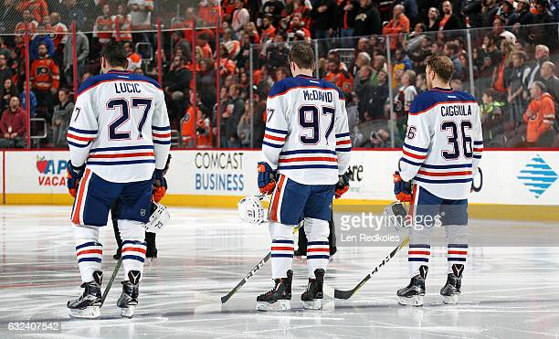 Milan Lucic Connor McDavid and Drake Caggiula of the Edmonton Oilers stand on the blue line during the National Anthem prior to their game against...