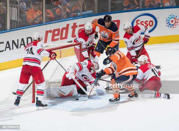 Milan Lucic looks on as teammate Mark Letestu of the Edmonton Oilers takes a shot on goaltender Cam Ward of the Carolina Hurricanes as Carolina's...