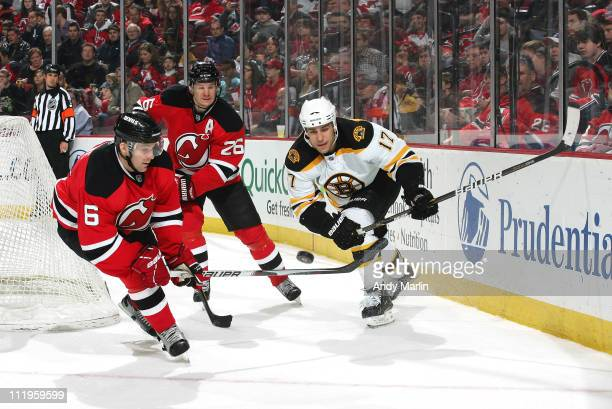 Milan Lucic of the Boston Bruins and Andy Greene of the New Jersey Devils skate for a loose puck during the game at the Prudential Center on April 10...