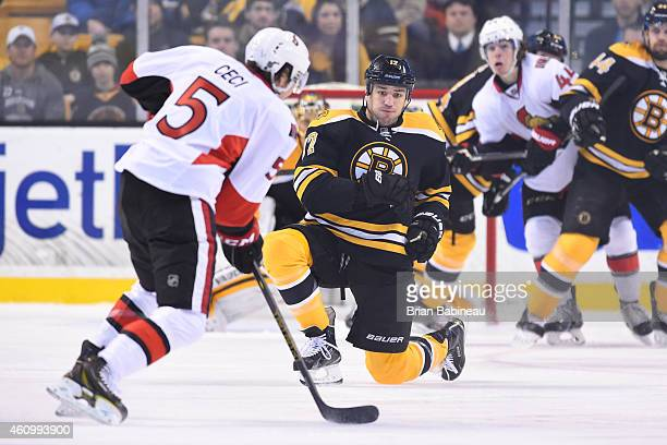 Milan Lucic of the Boston Bruins bends down to block the shot against Cody Ceci of the Ottawa Senators at the TD Garden on January 3 2015 in Boston...