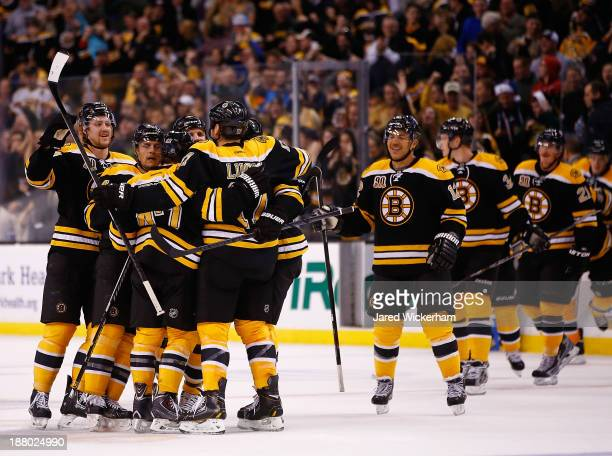 Milan Lucic of the Boston Bruins celebrates with his teammates after scoring the gamewinning goal in overtime against the Columbus Blue Jackets...