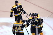 Milan Lucic of the Boston Bruins celebrates with his teammates Nathan Horton David Krejci and Dennis Seidenberg after scoring a goal in the third...