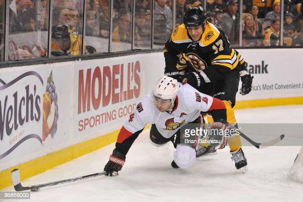 Milan Lucic of the Boston Bruins checks against Chris Philips of the Ottawa Senators at the TD Garden on January 18 2010 in Boston Massachusetts