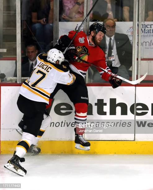 Milan Lucic of the Boston Bruins checks Bryan Bickell of the Chicago Blackhawks in Game Five of the 2013 NHL Stanley Cup Final at United Center on...