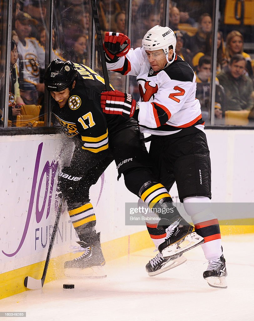 Milan Lucic #17 of the Boston Bruins fights for the puck against Marek Zidlicky #2 of the New Jersey Devils at the TD Garden on January 29, 2013 in Boston, Massachusetts.