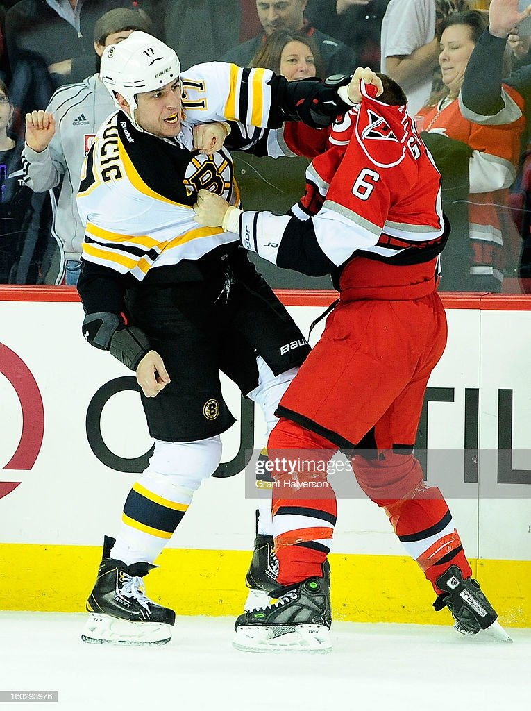 Milan Lucic #17 of the Boston Bruins fights with Tim Gleason #6 of the Carolina Hurricanes during play at PNC Arena on January 28, 2013 in Raleigh, North Carolina.